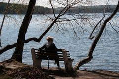 一条长凳的女孩由湖 库存照片