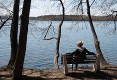 一条长凳的女孩由湖 免版税图库摄影