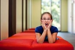 一条长凳的小女孩在一间晴朗的屋子 库存图片