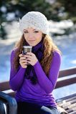 一条长凳的美丽的女孩与一杯咖啡在冬天 免版税库存照片