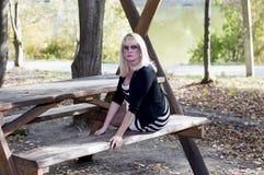 一条长凳的美丽的金发碧眼的女人在湖的公园 库存图片