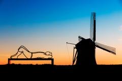 一条长凳的说谎的人在风车de巨人 库存照片