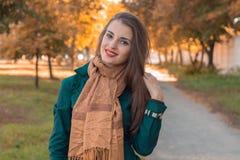 一条长的棕色围巾的微笑的少妇在街道上站立 图库摄影
