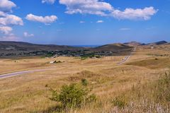 一条长的空的路,穿过用在山中的草盖的一个干燥谷反对蓝色多云天空 安排 库存图片