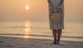 一条长的裙子的女孩在他的手上拿着在朝阳的背景的一个草帽 早晨在海滩走 库存照片