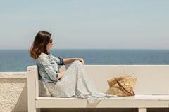 一条长的裙子的年轻美丽的妇女坐在backg的一条长凳 库存照片