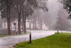 一条雨湿路的曲线在大雨中 免版税库存图片