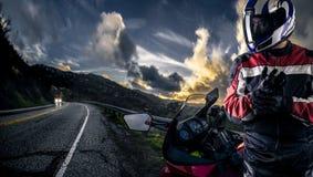 一条风景路的摩托车骑自行车的人 免版税库存照片