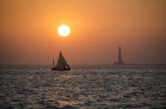 一条风船在日落期间的海与一座灯塔在背景中 库存照片