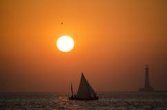 一条风船在日落期间的海与一座灯塔在背景中 图库摄影