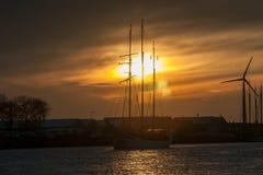 一条风船的帆柱在落日的光芒的 库存照片