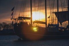 一条风船的帆柱在落日的光芒的 免版税库存图片