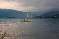 一条风船的某些人在湖 免版税库存图片