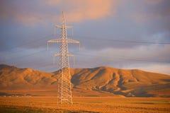 一条高压输电线的支持以晚上山为背景的 阿塞拜疆 免版税图库摄影