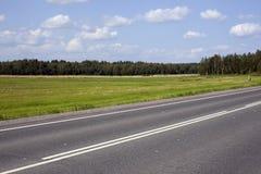 一条高速公路在与白色云彩的蓝天下  免版税库存图片