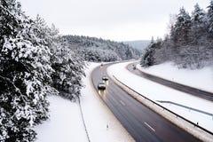 一条高速公路的美丽的景色在冬日 驾车通过用雪盖的杉木森林 图库摄影