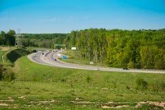 一条高速公路的轮有绿色森林的在右边 库存照片