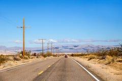 一条高速公路通过一个晴朗的内华达沙漠风景 图库摄影
