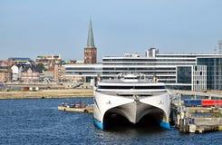 一条高速轮渡在奥尔胡斯停泊了丹麦港口  在背景现代和历史建筑能被看见 免版税库存照片