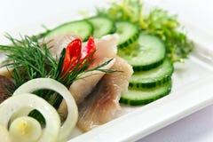 一条鲱鱼的内圆角用黄瓜 库存图片
