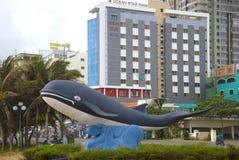 一条鲸鱼,头顿,越南的城市雕塑以现代旅馆为背景的 免版税图库摄影