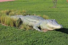 一条鳄鱼的雕塑在装饰公园的绿色草坪的 图库摄影