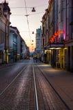 一条鹅卵石城市街道的晚上视图有电车轨道的 库存图片