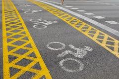 一条黄色自行车道路穿过路 人去 免版税库存照片
