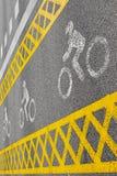一条黄色自行车道路穿过路 免版税库存图片