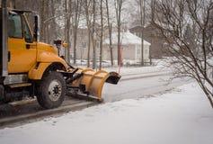 一条黄色除雪机清洁街道的看法在住宅neighbo的 库存图片