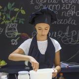 一条黑围裙和厨师` s帽子的俏丽的女孩厨师搅动与sp 库存图片