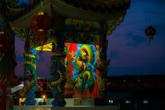 一条龙的雕象在杆的 中国灯笼红色 中国寺庙 反对蓝天的黑剪影 免版税图库摄影