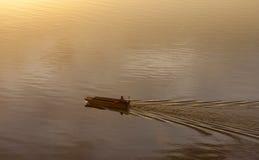 一条移动的小船的剪影在日出的在沙巴,马来西亚 库存图片