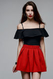 一条黑女衬衫和红色裙子的美丽的女孩 免版税库存照片