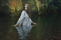 一条黑暗的不可思议的小河的美丽的妇女 免版税库存照片