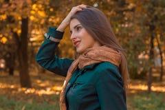 一条黑暗的衬衣和围巾的女孩在公园站立斜向一边握手头发 免版税图库摄影