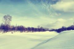 一条冻河的美好的冬天风景 免版税库存图片
