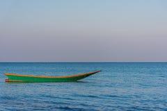 一条绿色老木长尾巴小船在安静海仍然漂浮在 图库摄影