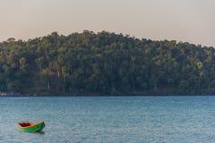 一条绿色老木长尾巴小船在安静海仍然漂浮在 免版税库存图片