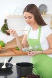 一条绿色围裙的年轻愉快的妇女烹调在厨房里的 主妇发现了她的汤的一份新的食谱 健康食物和 免版税库存照片