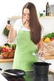一条绿色围裙的年轻白种人妇女烹调在厨房里的 主妇由木匙子品尝汤 食物和 图库摄影
