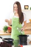 一条绿色围裙的年轻白种人妇女烹调在厨房里的 主妇由木匙子品尝汤 食物和 免版税库存照片