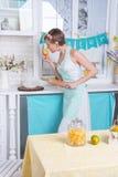 一条围裙的一个女孩在厨房里 库存照片