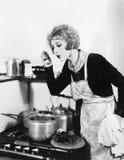 一条围裙的少妇在她的品尝她的从罐的厨房里食物(所有人被描述不是更长的生存和没有庄园exis 免版税库存照片