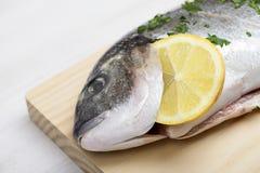 一条aw在一个木板的鱼用柠檬和绿色的特写镜头 免版税库存图片