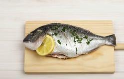 一条aw在一个木板的鱼用柠檬和绿色的特写镜头 库存照片