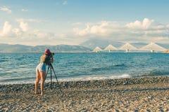 一条T恤杉和紧的裤子的拍Rion-Antirion桥梁的照片女孩在与三脚架的海滩和照相机 帕特雷 希腊 免版税库存图片
