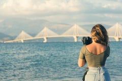 一条T恤杉和紧的裤子的拍Rion-Antirion桥梁的照片女孩有三脚架的和照相机 帕特雷 希腊 免版税库存图片