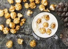 一杯与乳脂状的泡沫的味道好的鲜乳咖啡冠上了用在一块灰色石头的焦糖酥脆玉米花 免版税库存照片