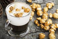 一杯与乳脂状的泡沫的味道好的鲜乳咖啡冠上了用在一块灰色石头的焦糖酥脆玉米花 库存照片